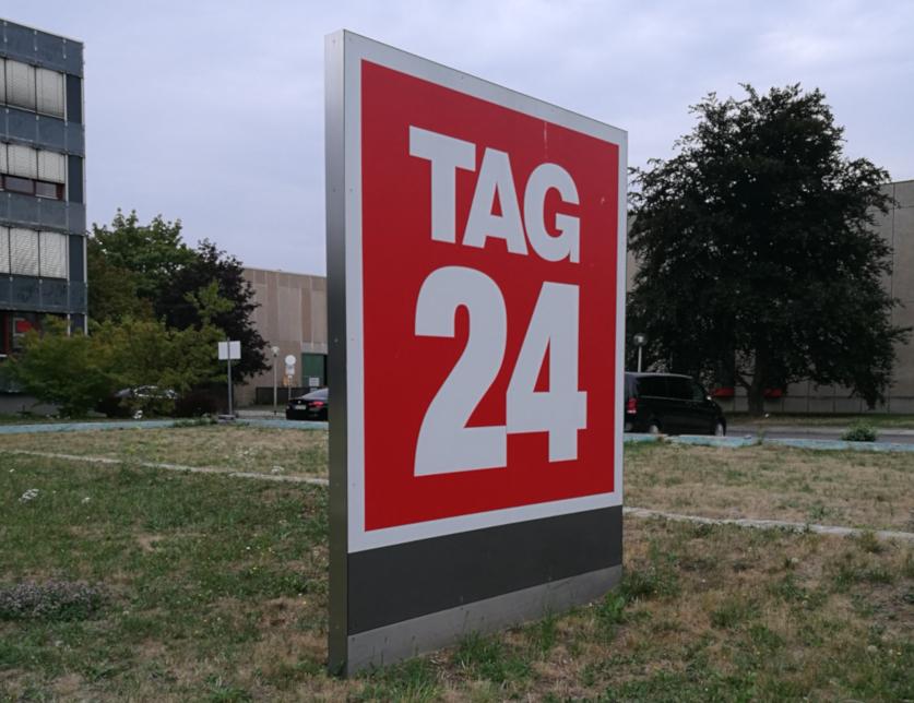 TAG24-Leuchtschild auf einem ausgetrockeneten Rasen vor der Firmenzentrale in Dresden.